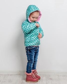 Bambina che allaccia la sua giacca blu