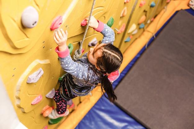 Bambina che arrampica una parete della roccia dell'interno
