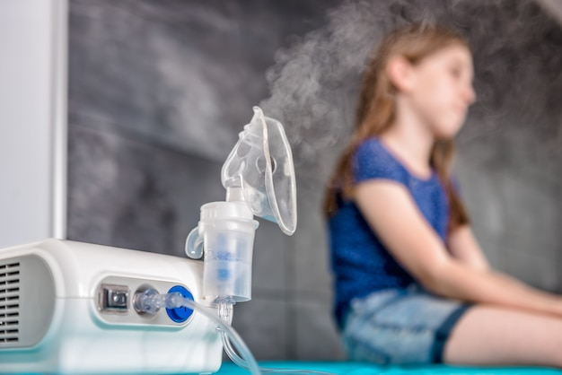 Bambina che aspetta trattamento medico per inalazione con un nebulizzatore