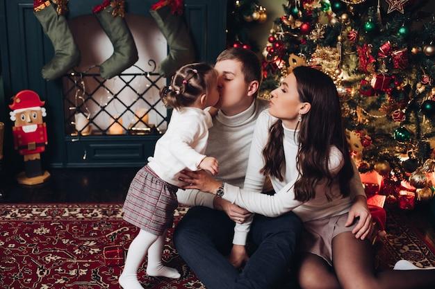 Bambina che bacia sua madre con amore a natale.
