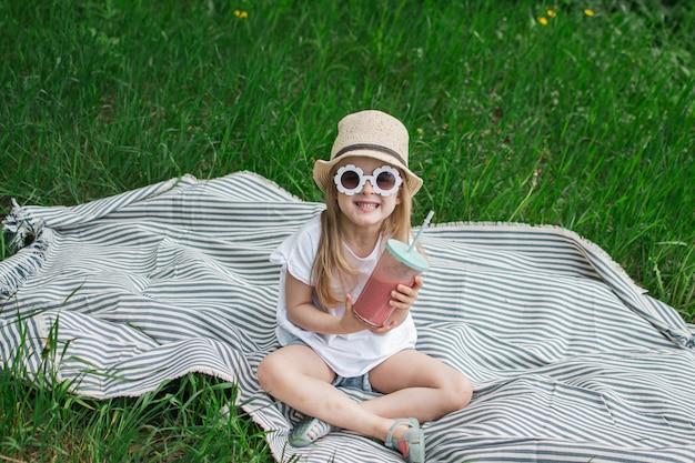 Bambina che beve il frullato delizioso della fragola con latte e gelato, all'aperto, concetto di estate, alimento sano