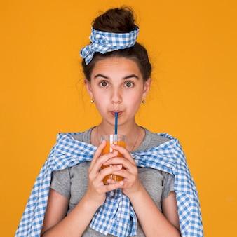 Bambina che beve un certo succo d'arancia