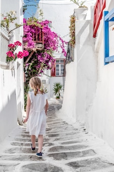 Bambina che cammina il vicolo stretto in grecia