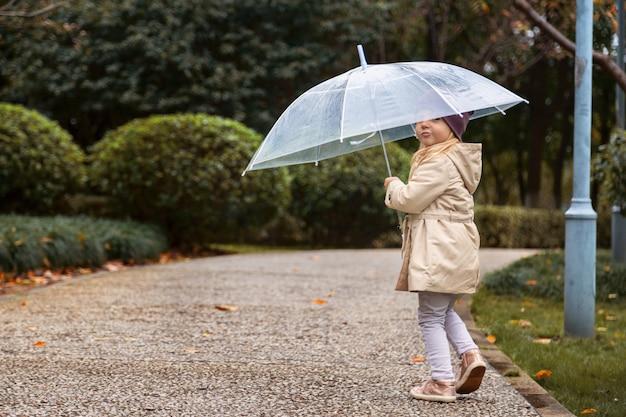 Bambina che cammina in un parco sotto un ombrello durante una pioggia