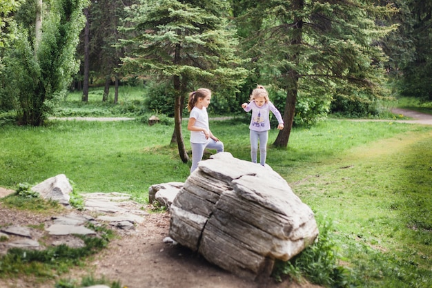 Bambina che cammina nel parco in estate, grandi rocce, arrampicata, escursionismo, sorella, ragazze