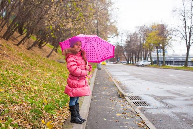 Bambina che cammina sotto un ombrello nel giorno piovoso di autunno