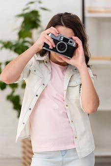 Bambina che cattura una foto con una macchina fotografica
