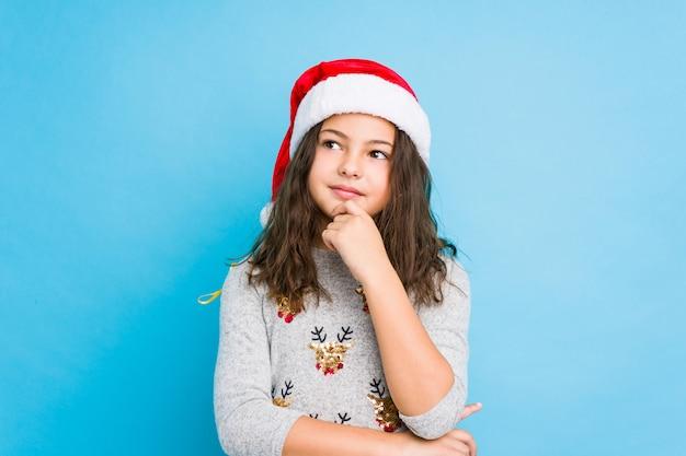 Bambina che celebra il giorno di natale che guarda lateralmente con espressione dubbiosa e scettica.
