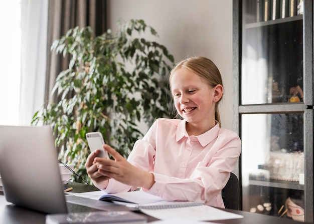 Bambina che controlla il suo telefono nella classe