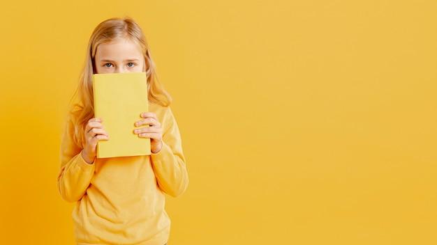 Bambina che copre il viso con il libro