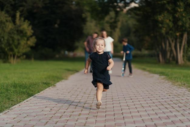 Bambina che corre mentre la sua famiglia la segue