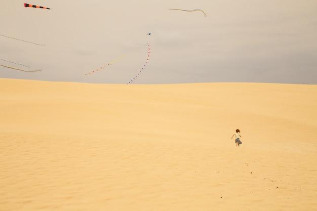 Bambina che corre verso un'area in cui gli aquiloni volano tra le dune di sabbia di una spiaggia