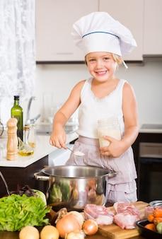 Bambina che cucina con carne