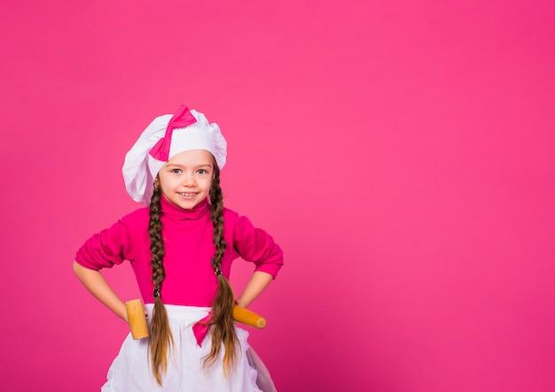 Bambina che cucina in piedi con utensili da cucina
