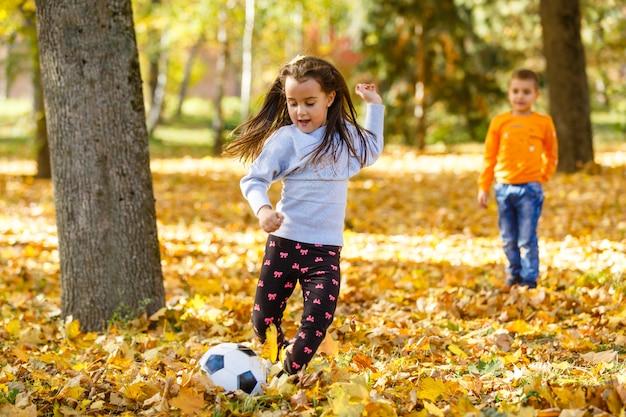 Bambina che dà dei calci alla palla nel parco di autunno