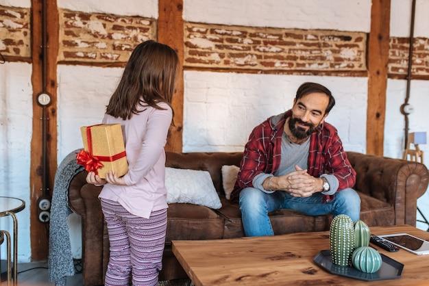 Bambina che dà un regalo a sorpresa o suo padre sul divano di casa il giorno del padre