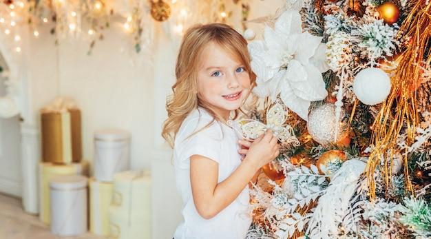 Bambina che decora l'albero di natale alla vigilia di natale a casa. ragazzino nella stanza leggera con la decorazione di inverno. tempo per il concetto di celebrazione banner