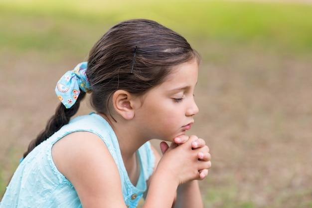 Bambina che dice le sue preghiere