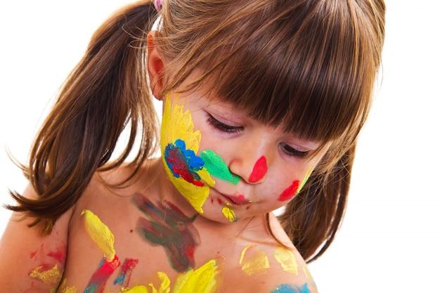Bambina che dipinge con pennello e vernici colorate