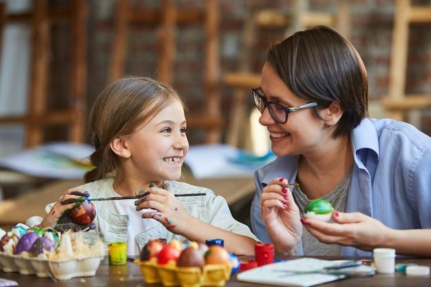Bambina che dipinge le uova di pasqua con la mamma