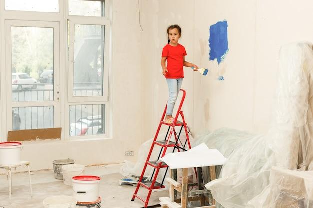 Bambina che dipinge una parete a casa