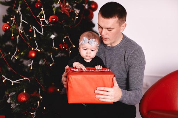 Bambina che disimballa regalo con il papà vicino all'albero di natale la bambina felice disimballa il contenitore di regalo di feste. famiglia adorabile felice.