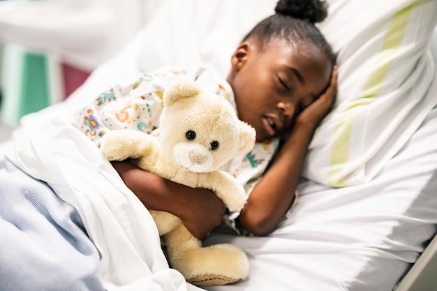 Bambina che dorme in un letto d'ospedale