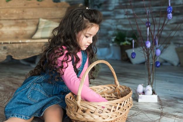 Bambina che esamina canestro vicino alle uova di pasqua