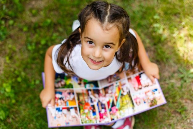Bambina che esamina la sua foto dell'album
