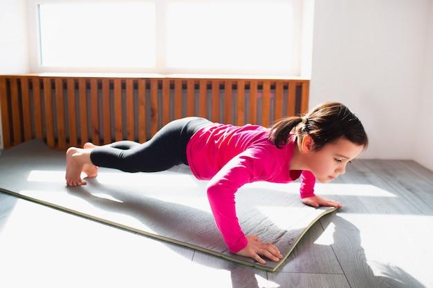 Bambina che fa allenamento di piegamenti sulle braccia a casa. ragazzo carino si sta allenando su una stuoia al coperto. la piccola modella mora in abiti sportivi ha esercizi vicino alla finestra nella sua stanza