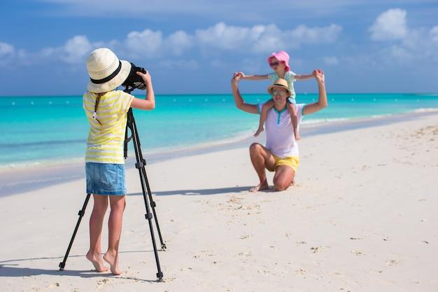 Bambina che fa foto del suoi papà e sorella alla spiaggia