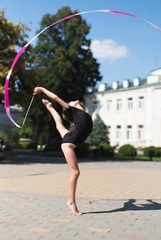 Bambina che fa ginnastica in parco
