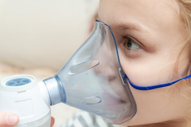 Bambina che fa inalazione con il nebulizzatore a casa. bambina con inalatore. primo piano, messa a fuoco selettiva