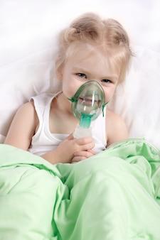 Bambina che fa inalazione sdraiato nel letto