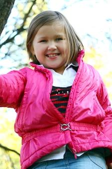 Bambina che fa passeggiata sana attraverso il parco di autunno