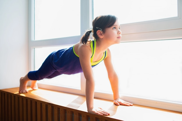 Bambina che fa un allenamento di esercizio della plancia a casa. ragazzo carino si sta allenando su un davanzale in legno al coperto. la piccola modella mora in abiti sportivi ha esercizi vicino alla finestra nella sua stanza.