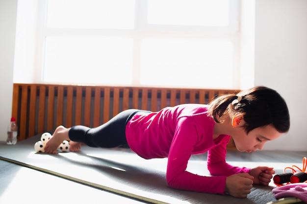 Bambina che fa un allenamento di esercizio della plancia a casa. ragazzo carino si sta allenando su una stuoia al coperto. la piccola modella mora in abiti sportivi ha esercizi vicino alla finestra nella sua stanza