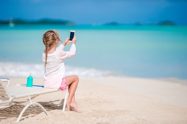 Bambina che fa video o foto con dalla sua macchina fotografica che si siede sul lettino