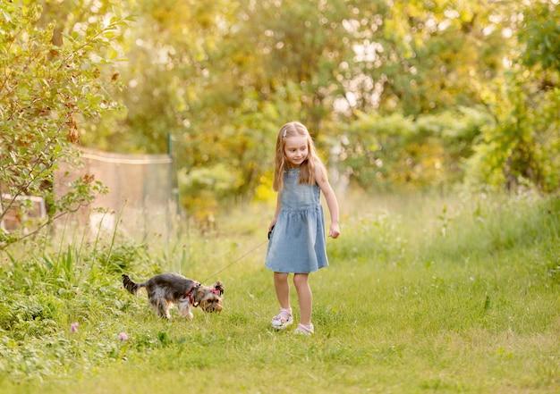 Bambina che funziona con il cane nella campagna