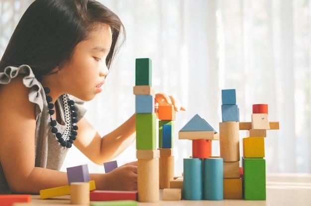 Bambina che gioca con i blocchetti del giocattolo della costruzione che costruiscono una torre