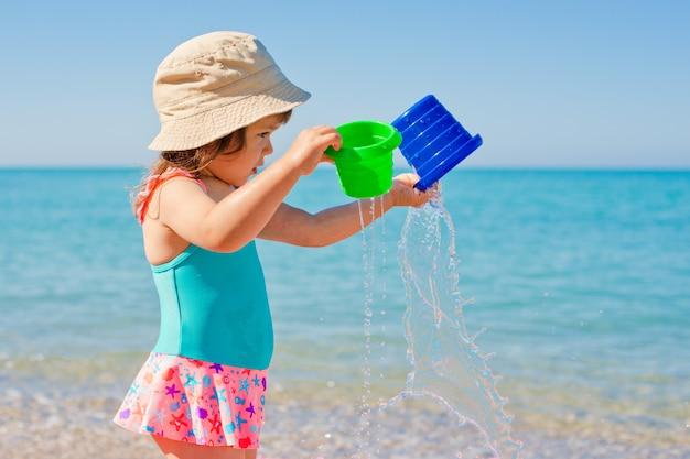 Bambina che gioca con i giocattoli in vacanza al mare