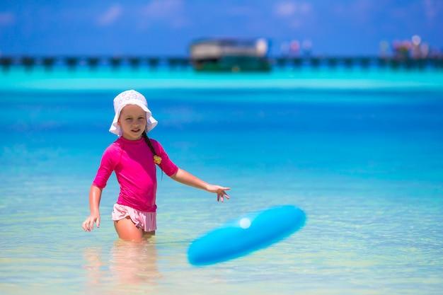 Bambina che gioca con il disco volante alla spiaggia bianca