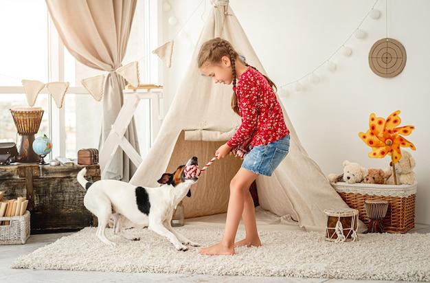 Bambina che gioca con il fox terrier