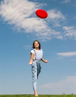 Bambina che gioca con il frisbee all'aperto