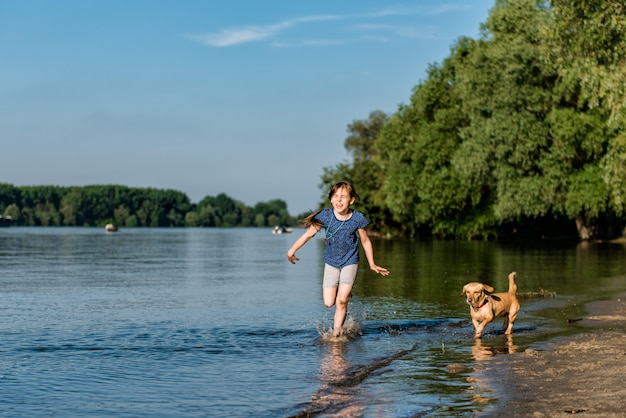 Bambina che gioca con il suo cane nel fiume