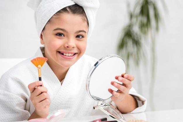 Bambina che gioca con la sua spazzola illuminatore di madri