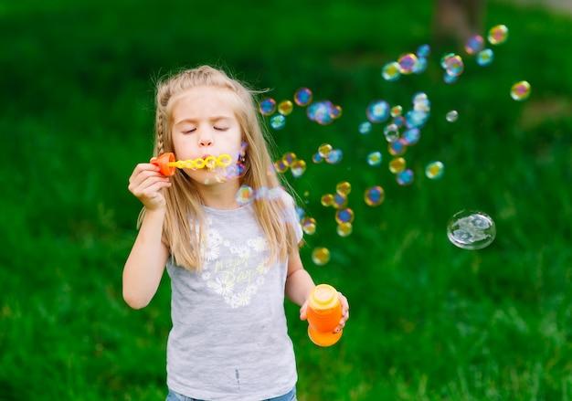 Bambina che gioca con le bolle di sapone.