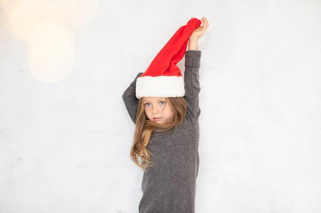 Bambina che gioca con un cappello di babbo natale