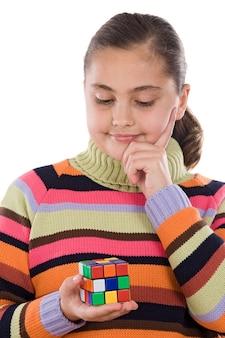 Bambina che gioca con un cubo colorfull isolato su bianco