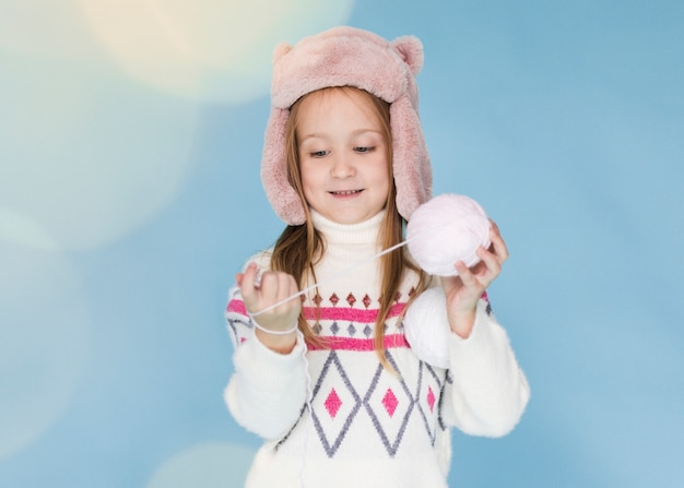 Bambina che gioca con un gomitolo di lana